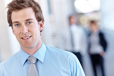 Buy stock photo Handsome young businessman standing and smiling with blurred businesspeople in the background