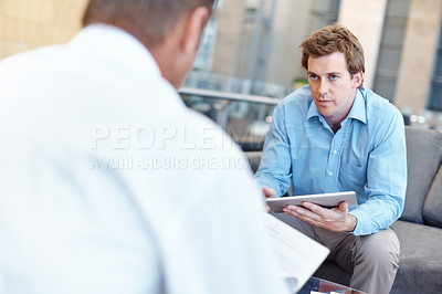 Buy stock photo Young businessman using a tablet during a meeting with a mature businessman