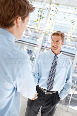 Buy stock photo Two businessmen shaking hands while standing indoors