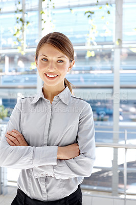 Buy stock photo Beautiful young businesswoman standing and smiling with her arms folded