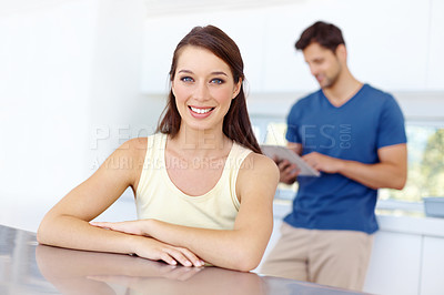 Buy stock photo A woman sitting at her kitchen table with her boyfriend in the background looking at his tablet