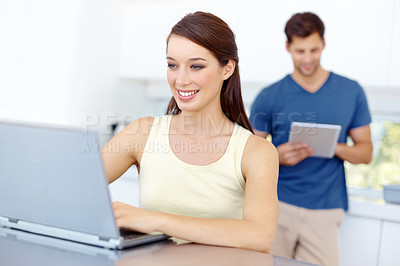 Buy stock photo A woman sitting at her kitchen table with her loptop while her boyfriend in the background looking at his tablet