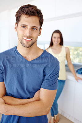 Buy stock photo Portrait of a handsome man folding his arms with his girlfriend in the background
