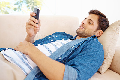 Buy stock photo Man relaxing on his couch texting on his cellphone
