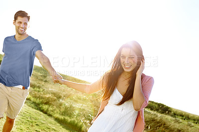 Buy stock photo A happy couple walking through a field holding hands