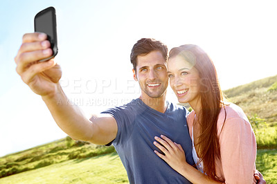 Buy stock photo A couple in a field taking a picture of themselves with a cellphone