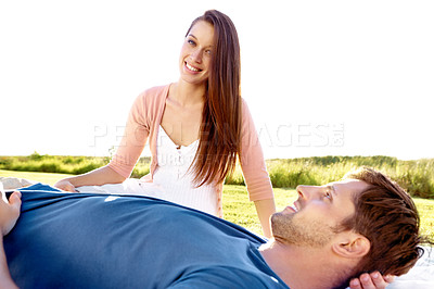 Buy stock photo A couple in a field with the boyfriend lying his girlfriend's lap while they share an intimate moment