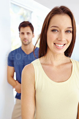 Buy stock photo Close up portrait of an attractive young woman with her husband standing in the background