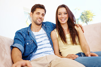 Buy stock photo Portrait of a happy young couple sitting on a sofa in their living room and smiling at the camera
