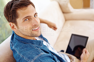 Buy stock photo High angle portrait of a handsome young man sitting on a sofa and using a digital tablet