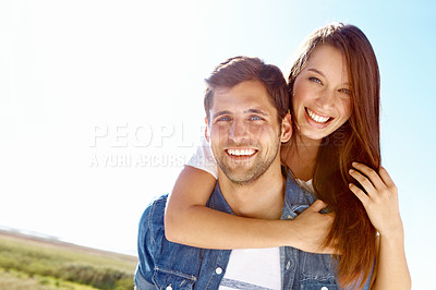 Buy stock photo Portrait of a young man giving his wife a piggyback while walking in a field