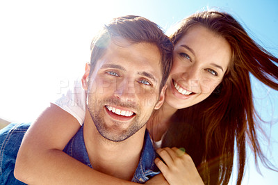 Buy stock photo Close up portrait of a man giving his wife a piggyback while going for a walk outside