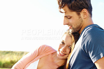Buy stock photo Portrait of a young woman resting her head on her boyfriend's chest while enjoying a sunny day out
