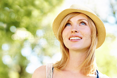 Buy stock photo A beautiful blonde with a hat on looking upwards in the park