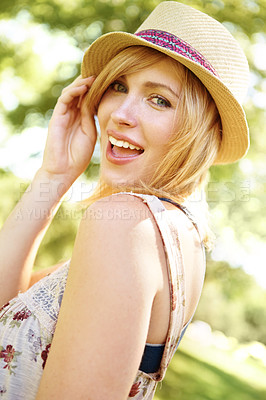 Buy stock photo A beautiful young woman wearing a sunhat and looking over her shoulder at the camera