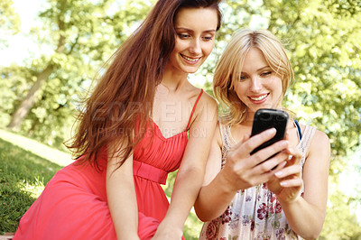 Buy stock photo Two beautiful friends using a cell phone in a park