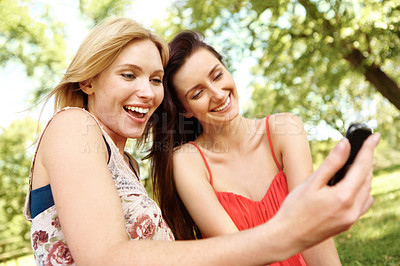Buy stock photo Two beautiful friends taking a self portrait in a park