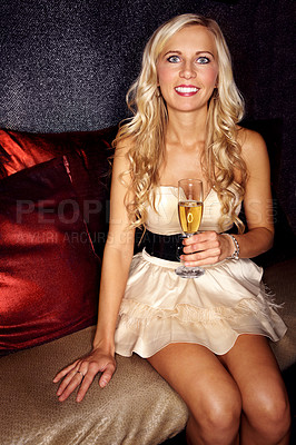 Buy stock photo Portrait of an attractive blonde woman sitting on a sofa in a nightclub drinking champagne