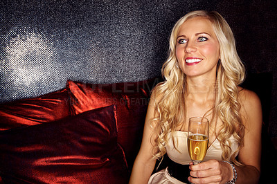 Buy stock photo Shot of an attractive blonde woman sitting on a sofa in a nightclub drinking champagne