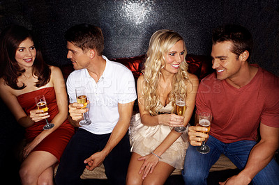Buy stock photo Shot of four good-looking young people drinking champagne while sitting in a nightclub together