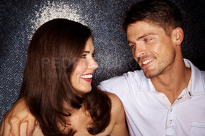 Buy stock photo Shot of a good-looking young couple staring at each other while out on a night on the town