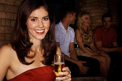 Buy stock photo Portrait of an attractive woman drinking champagne with her friends sitting behind her