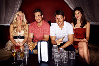 Buy stock photo Portrait of four good-looking young people drinking champagne while sitting in a nightclub together