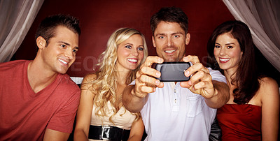Buy stock photo Shot of four friends taking a self-portrait of each other on a camera phone