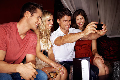 Buy stock photo Shot of a four friends taking a group self-portrait on a camera phone while sitting in a club