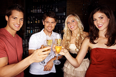 Buy stock photo Portrait of four young people drinking champagne on a night out on the town