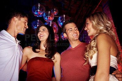 Buy stock photo Low angle shot of four young people standing in a nightclub under some disco balls