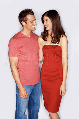 Buy stock photo Studio shot of a good-looking young couple standing arm in arm and looking at each other