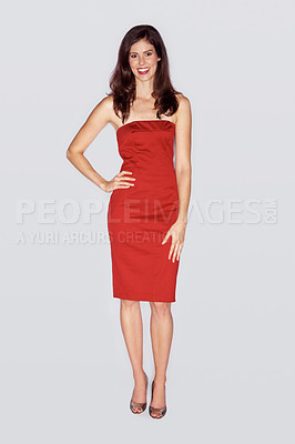 Buy stock photo Full length studio portrait of an attractive woman dressed in a red cocktail dress with her hand on her hip