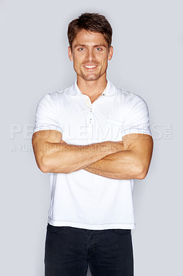 Buy stock photo Studio portrait of a handsome young man standing with his arms folded