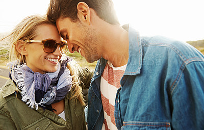 Buy stock photo A young couple looking lovingly into one anothers' eyes while on a roadtrip