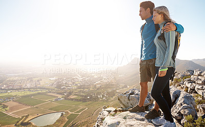 Buy stock photo Young couple admiring the view while out hiking together