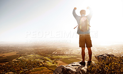 Buy stock photo Rearview of a male hiker standing at the top of a mountain and feeling victorious