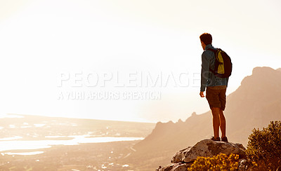 Buy stock photo Rear view of a male hiker standing at the top of a mountain