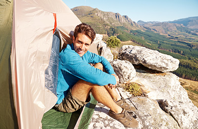 Buy stock photo Handsome young man sitting in his tent on a mountain top