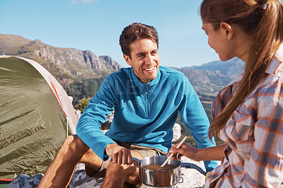 Buy stock photo Cute young couple smiling while on a camping trip together and making some hot chocolate
