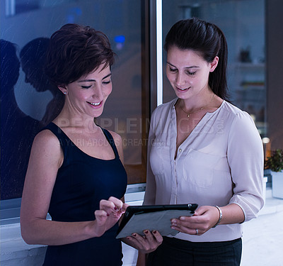 Buy stock photo Shot of two businesswomen working with a digital tablet late at night. Real life businesspeople shot on location. Since these locations are the real thing, and not shot in an