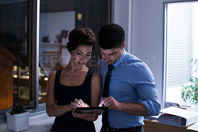 Buy stock photo Shot of two businesspeople working with a digital tablet late at night. Real life businesspeople shot on location. Since these locations are the real thing, and not shot in an