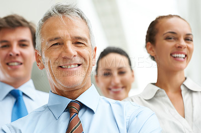 Buy stock photo Closeup of successful senior businessman with his team in background smiling