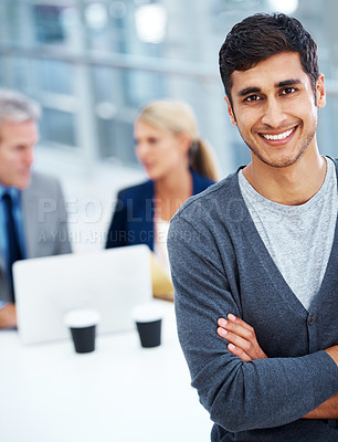Buy stock photo A handsome young man smiling in the office with his colleagues in the background