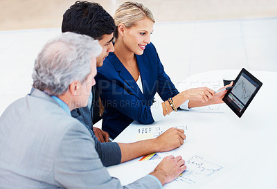 Buy stock photo A group of businesspeople looking together at a graph on a digital tablet