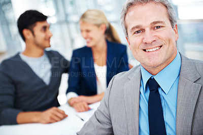 Buy stock photo A handsome mature businessman smiling at the camera with his colleagues in the background