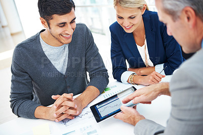 Buy stock photo A group of businesspeople working together on a digital tablet