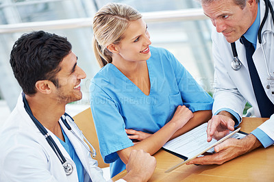 Buy stock photo A group of doctors looking together at something on a digital tablet