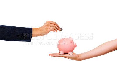 Buy stock photo Cropped image of a woman's hand placing a coin into a piggy bank being held by another hand