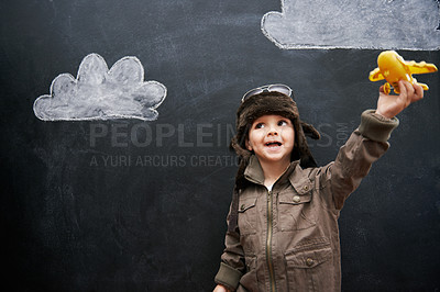 Buy stock photo A little boy playing with an airplane in front of clouds drawn on a blackboard